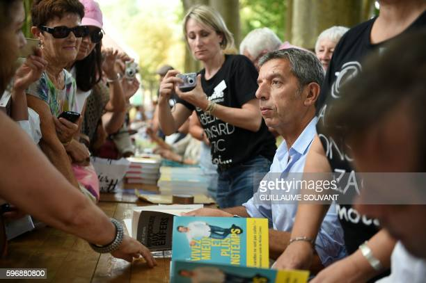 French TV host Michel Cymes dedicates his last book on August 28 2016 in ChanceauxprèsLoches central France during the 21th book fair 'The book...