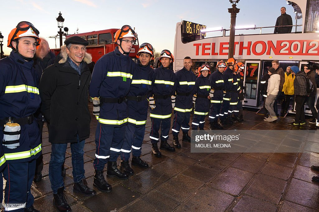 French TV host Nagui (2ndL) poses with firefighters during a ceremony to launch the 26th Telethon, France's biggest annual fund-raising event on December 7, 2012 in Paris. The event, aiming at collecting funds for research on genetic diseases such as myopathy, a neuromuscular disease, will take place on December 7 and 8, 2011.