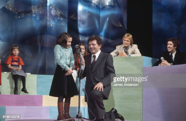 French TV host of 'L'Ecole des Fans' Jacques Martin welcomes the French singer Claude François and humorist Stéphane Collaro to the show During the...