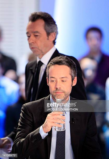 French TV host Yann Barthès is pictured next to TVhost Michel Denisot prior to takes part in his TV show 'Le petit journal' on a set of French TV...
