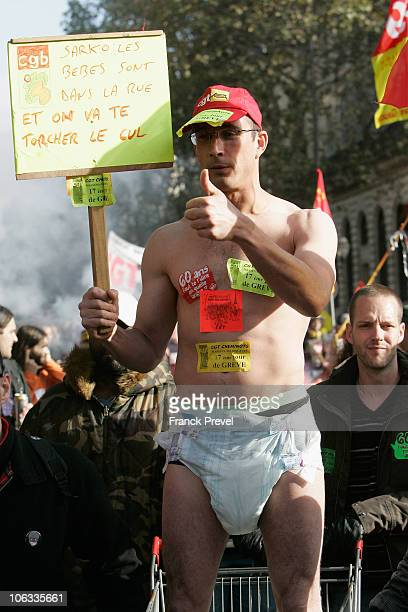 French university students and striking workers attend a demonstration over pension reforms a man with a diaper holds a placard 'Sarkozy babies are...