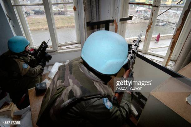 French UNPROFOR soldiers one a sharpshooter with a sightmounted long rifle the other with the standard French Famas assault gun protect a passage...
