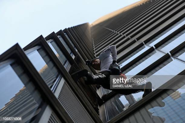 TOPSHOT French urban climber Alain Robert also known as 'SpiderMan' begins his climb of Heron Tower 110 Bishopsgate in central London on October 25...