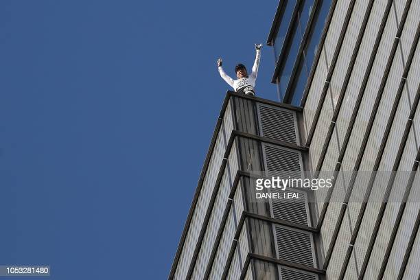TOPSHOT French urban climber Alain Robert also known as 'SpiderMan' reacts as he reaches the top of Heron Tower 110 Bishopsgate in central London on...