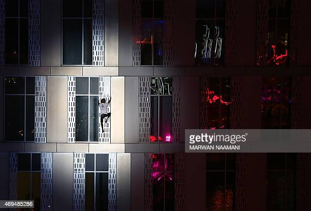 French urban climber Alain Robert also known as 'SpiderMan' scales the Cayan Tower the world's tallest twisted building on April 12 2015 in Dubai AFP...