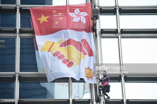TOPSHOT French urban climber Alain Robert popularly known as the French Spiderman secures a banner showing shaking hands below a depiction of the...