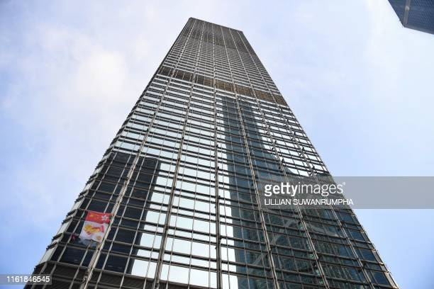 French urban climber Alain Robert popularly known as the French Spiderman secures a banner showing shaking hands below a depiction of the Chinese and...