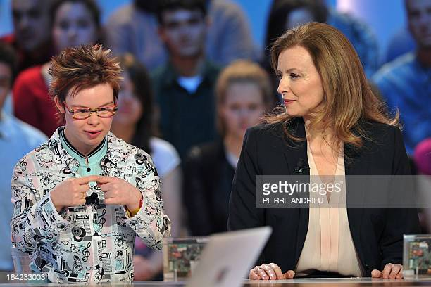 French Valerie Trierweiler the partner of French President listens to Eleonore a young girl with Down syndrome as she takes part on March 21 2013 in...