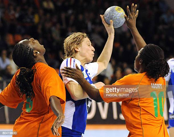 French Veronique PecqueuxRolland fights for the ball with Ivory Coast's Abony N'guessan Robeace and Paula Gondo Bredou on March 28 2008 in Nimes...