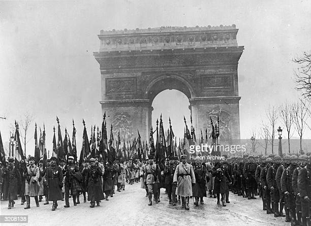 French veterans marching by the Tomb of the Unknown Soldier in Paris on the anniversary of Armistice Day In the background the Arc de Triomphe is...