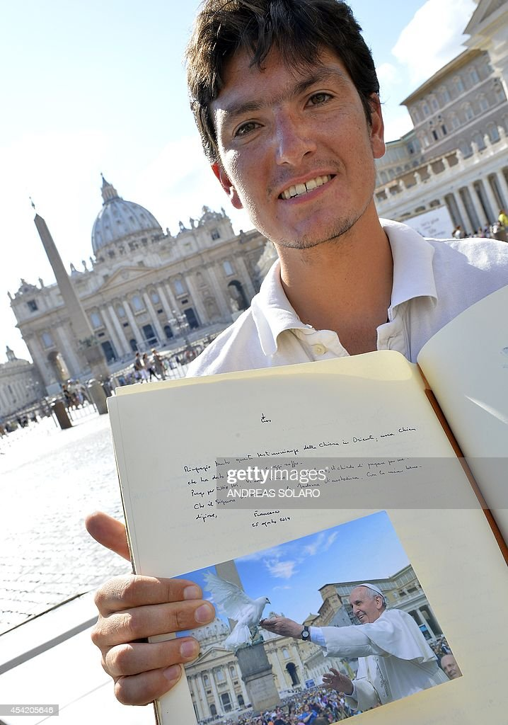 French Vincent Gelot, 26, poses with testimonial book on St. Peter's square, on August 26, 2014 at the Vatican. Vincent Gelot spent the past two years traveling around the world with his 4L car, visiting Christian communities in 23 countries and saving their testimonies in a large leather book which ends with a dedication by the Pope who wrote 'Thank you so much for this testimony of the Eastern Church, a church that has given so many saints and now suffer. I pray for you all, I am close to you.'