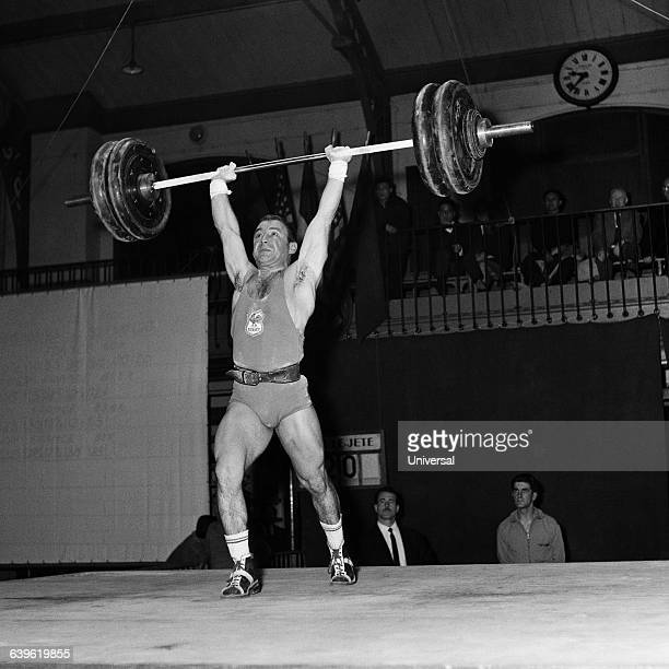 French weightlifter Pierre Fulla lifts the bar in the snatch event