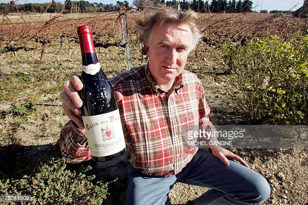 French wine producer PaulVincent Avril poses in his vineyard with a bottle of his 'Clos des Papes' 2005 grand cru named wine of the year by the US...