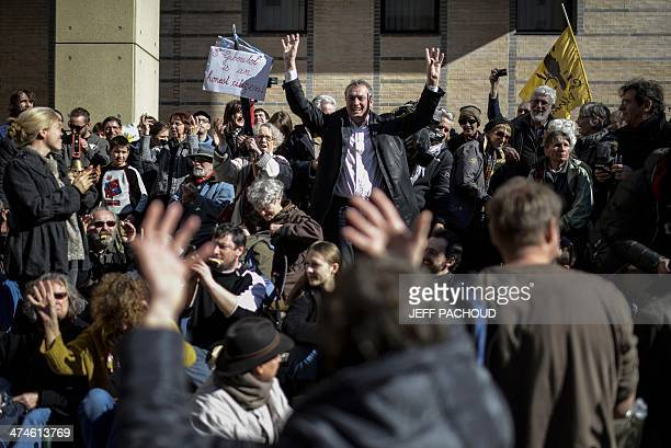 French winemaker Emmanuel Giboulot flanked by supporters sings 'Ban bourguignon' a traditional song before entering the court on February 24 2014 in...