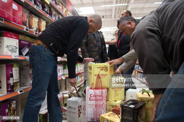French winemakers from the Gard department un pack wine packages during an unauthorized control of the origin of wines in a supermarket in Nimes on...