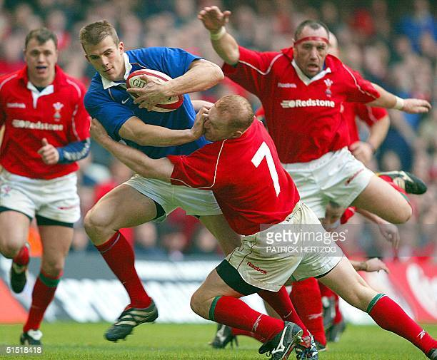 French winger Aurelien Rougerie is tackled by Welsh flanker Martyn Williams during the Wales/France 6 Nations rugby game 16 February 2002 at the...