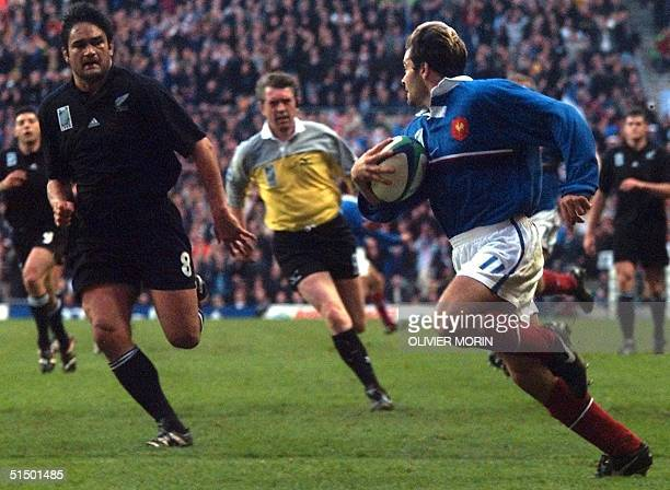 French winger Christophe Dominici is chased by New Zealand N8 and captain Taine Randell as he goes to score a try during the Rugby World Cup...