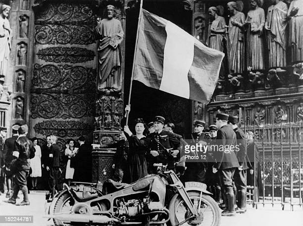 A French woman holds aloft the Tricolor in front of NotreDame Cathedral where Parisians gathered to offer prayers of thankgiving for their liberation