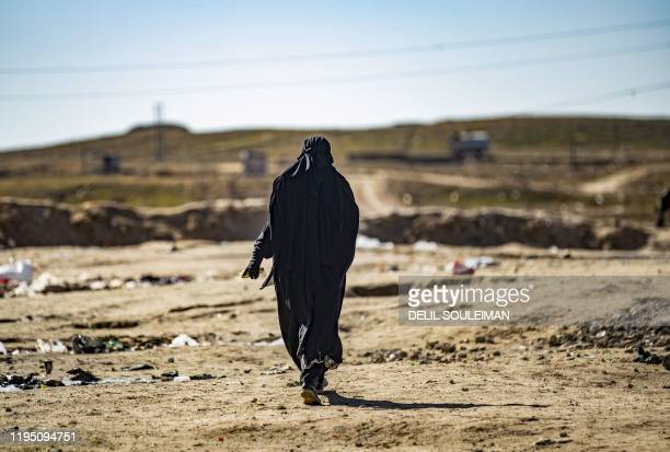 French woman named Um Muhammad walks at the section reserved for foreigners, inside the Kurdish-run al-Hol camp for the displaced in the al-Hasakeh...