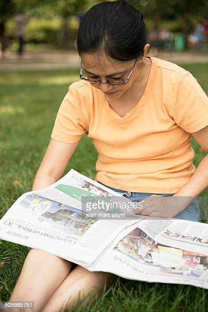 """French woman of asian origin sat on the grass in a park reading the newspaper """" The Parisian """" in the afternoon. Model release available"""