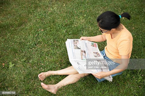 French woman of asian origin sat on the grass in a park reading the newspaper ' The Parisian ' in the afternoon near Paris in France Model release...
