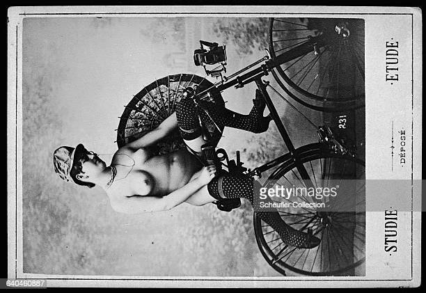 A French woman poses nude for a photograph sitting on a bicycle