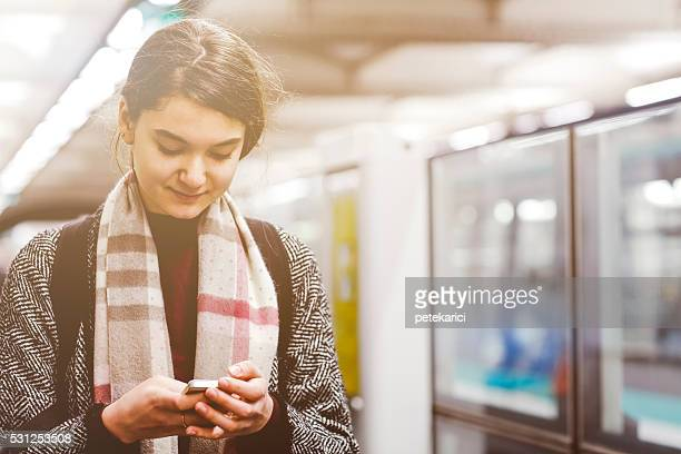 French woman using a smartphone on the metro subway station
