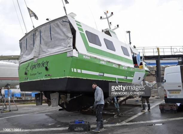 French workers repair L'Epervier on November 29 a boat that was stolen and damaged by migrants who tried to cross the English Channel in Wissant...