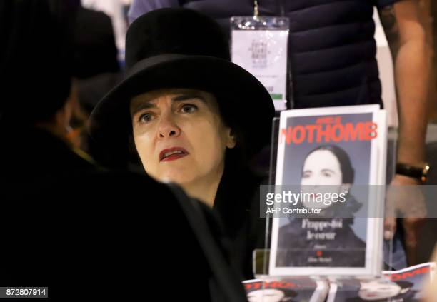 French writer Amelie Nothomb meets a reader during the 36th edition of the 'Foire du Livre de Brive' book fair on November 11 2017 in...