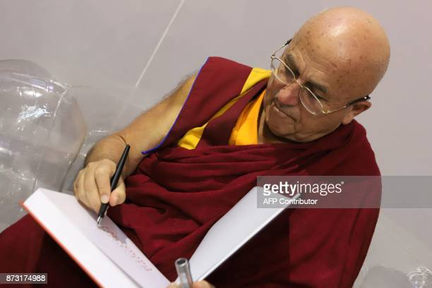 French writer and Buddhist monk Matthieu Ricard signs his book during the 36th edition of the 'Foire du Livre de Brive' book fair on November 12 2017...