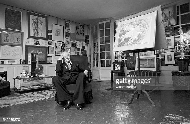 French writer and poet Louis Aragon at home with a photograph of his partner, poet, translator and writer Elsa Triolet, behind him.