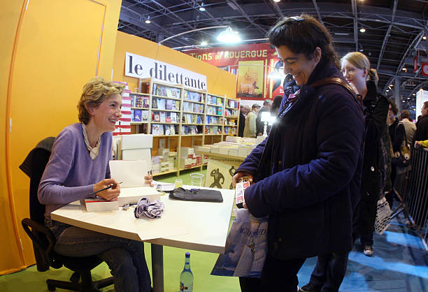 French writer Anna Gavalda (L) signs her Pictures | Getty Images on