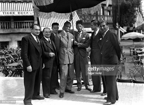 French writer artist and filmmaker Jean Cocteau holding a parasol over Panamanian bantamweight boxer Panama Al Brown 1925 Brown's trainer Bob Robert...