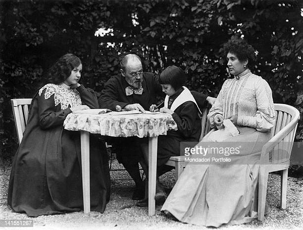 French writer Emile Zola sitting at a table in the garden of his house between his children Jacques e Denise and with his partner Jeanne Rozerot...