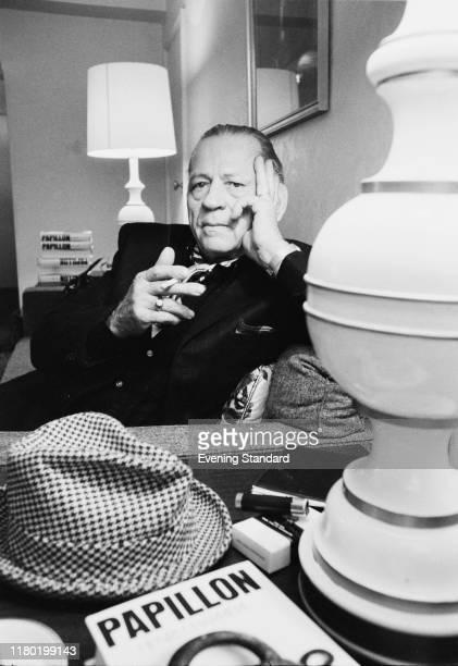 French writer Henri Charrière smoking a cigarette UK 30th May 1970