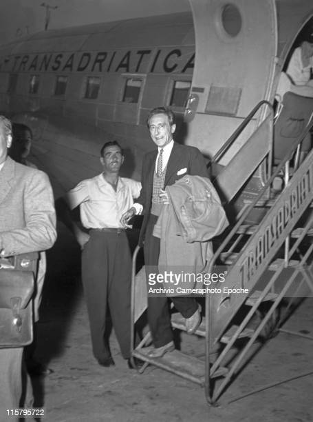 French writer Jean Cocteau with a striped tie holding his coat getting down an airplane at the Marco Polo airport Tessera for the Movie Festival...