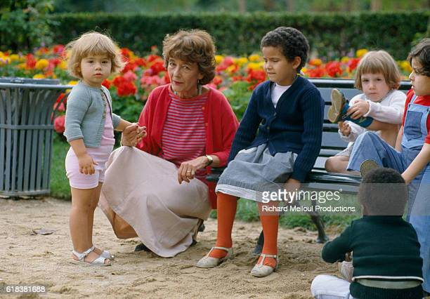 French writer Laurence Pernoud sits at a playground with a group of young children. Pernoud in author of books on parenting.