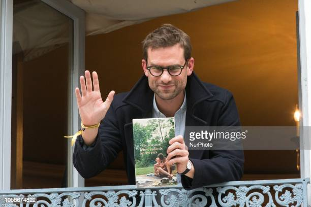 French writer Nicolas Mathieu poses with his book quotLeurs enfants apres euxquot on the balcony of Drouant restaurant after winning the Prix...