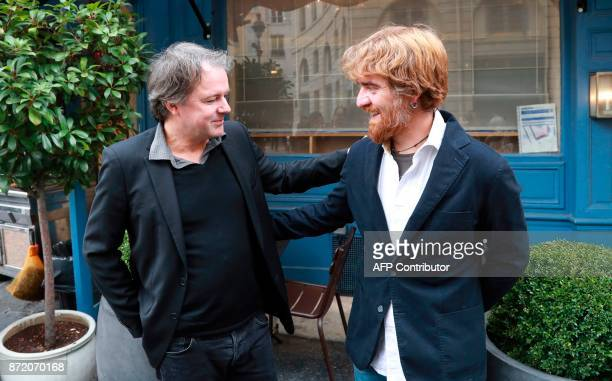 French writer Yannick Haenel and Italian writer Paolo Cognetti pose for pictures in front of the restaurant 'La Mediterranee' in Paris on November 9...