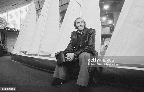 French yachtsman Alain Colas sits on the edge of a yacht on display at the CNIT center during the 1976 Paris Boat Show. In 1973, Colas became the...