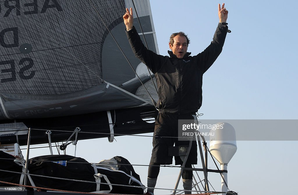 French yachtsman Marc Guillemot flashes the 'V' sign as he stands on his 'Safran' monohull upon his arrival on July 7, 2013 in La Trinite-sur-Mer, western France. Guillemot set a new record for a solo, single-hulled crossing of the north Atlantic Ocean, slicing more than 15 hours off the previous mark.