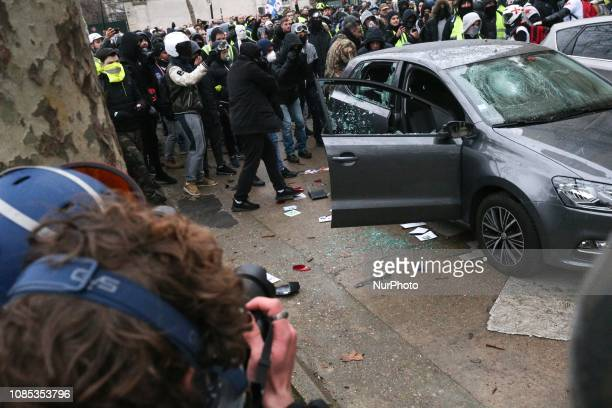 French yellow vests protesters vandalize a vehicle in front of the Hotel national voice over Invalides in Paris on January 19 2019 during a...