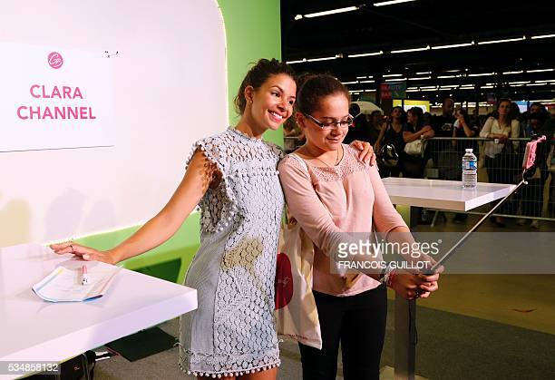 French YouTube personality Safia Vendome poses with a girl for a selfie during the Get Beauty fair a beauty and fashion fair inspired by the US...