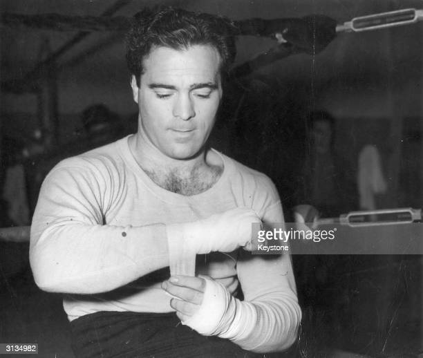 FrenchAlgerian middleweight boxer Marcel Cerdan tying tape around his hands before a training bout for his fight with George Ambers at Madison Square...