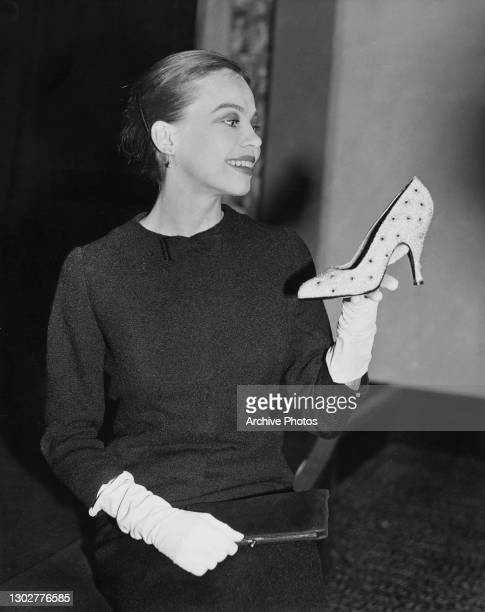 French-American actress, dancer, and writer Leslie Caron holding a dotted heeled shoe, US, circa 1960.