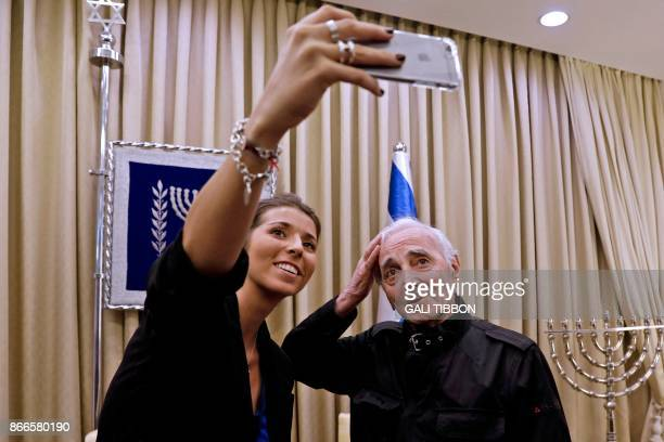 FrenchArmenian singer Charles Aznavour adjusts his hair as he does a selfie with a fan on October 26 2017 at the presidential compound in Jerusalem...