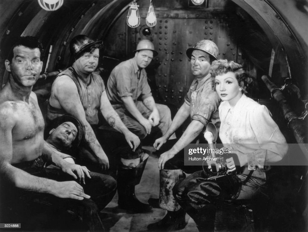 French-born actor Claudette Colbert holds a camera as she sits with a group of dirty men in a tunnel, including American actor Fred MacMurray (L), in a still from director Mitchell Leisen's film, 'No Time for Love'.