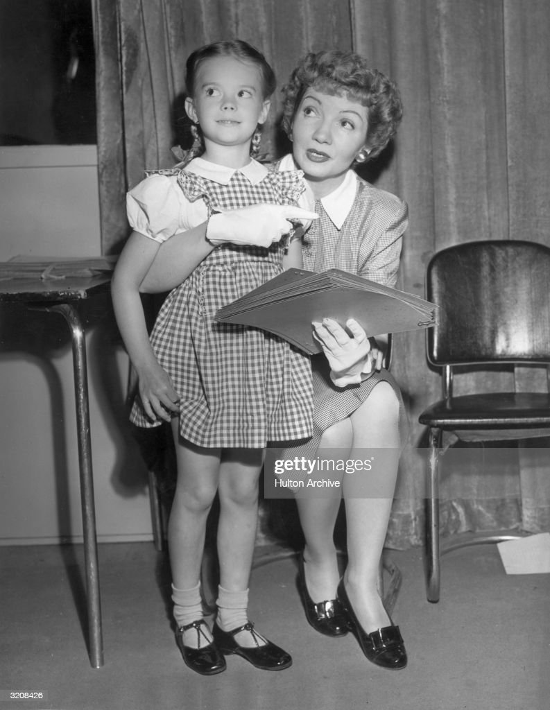 French-born actor Claudette Colbert (1903 - 1996) (right) talks and points as she sits with her arm around American child actor Natalie Wood and holds a script during a rehearsal for a Lux Radio Theater program, Hollywood, California. Wood is wearing a checkered jumper over a white shirt.