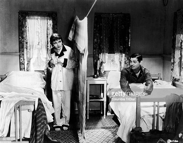 Frenchborn American actor Claudette Colbert stands on one side of a bedroom divided by a sheet hanging from a clothesline as American actor Clark...