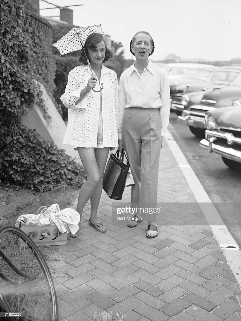 French-born American fashion editor Diana Vreeland (1906 - 1989) (right) and socialite Cordelia Robertson (1900 - 1984), both dressed casually, stand on the street probably in front of the Southampton Bathing Corporation, Southampton, New York, 1940s. Robertson holds a parasol to shield her head from the sun.